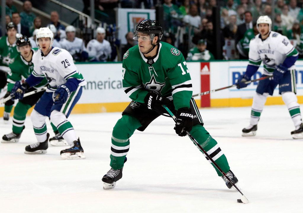Dallas Stars center Mattias Janmark (13) lines up a shot at the net during the first period of the team's NHL hockey game against the Vancouver Canucks in Dallas, Sunday, March 17, 2019. (AP Photo/Tony Gutierrez)