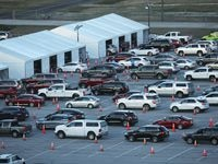 Vehicles line up at the drive-through COVID-19 vaccination clinic at Texas Motor Speedway in Fort Worth.