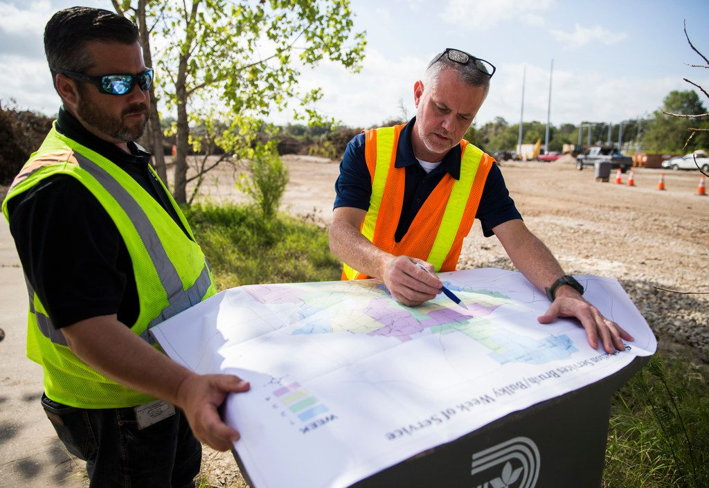 Tim Oliver (left), assistant director of Sanitation Services for the city of Dallas, and Kelly High, director of Sanitation Services, point out the hardest-hit areas of the city where debris needs to be collected at a temporary collection site near the intersection of  Highway 75 and Interstate 635 in Dallas on June 21.