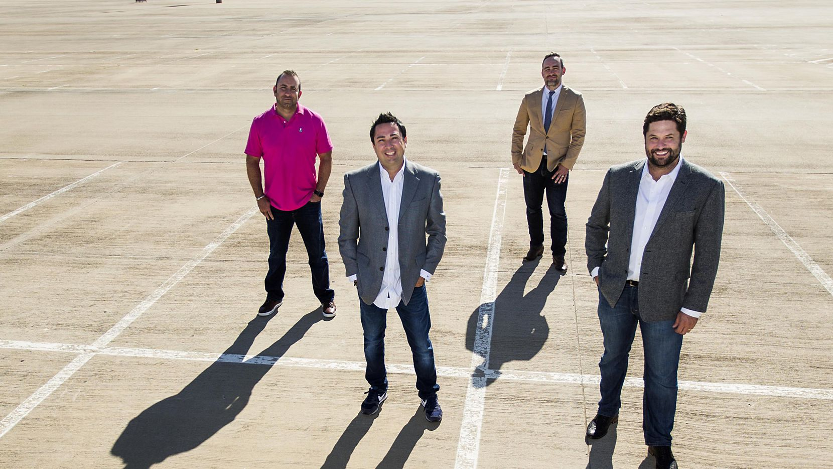ParkHub leaders, from left, Tony Albanese, President & CRO, George Baker, Founder & CEO, Dave Livingston, CTO, and Jake Edsell, COO, gather for a group picture in the lot at AT&T Stadium on Tuesday, Oct. 11, 2016, in Arlington, Texas.  (Smiley N. Pool/The Dallas Morning News)