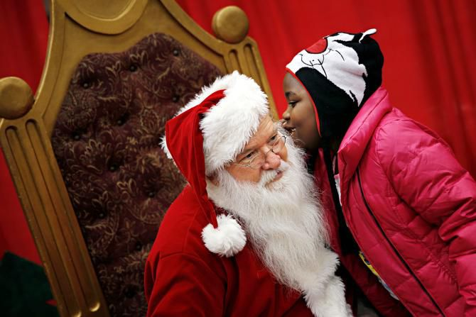 Ky'liah Ware whispered a wish to Santa Claus. Families lined up in the early morning hours on Saturday to enjoy a hot meal, haircut and other donated gifts.
