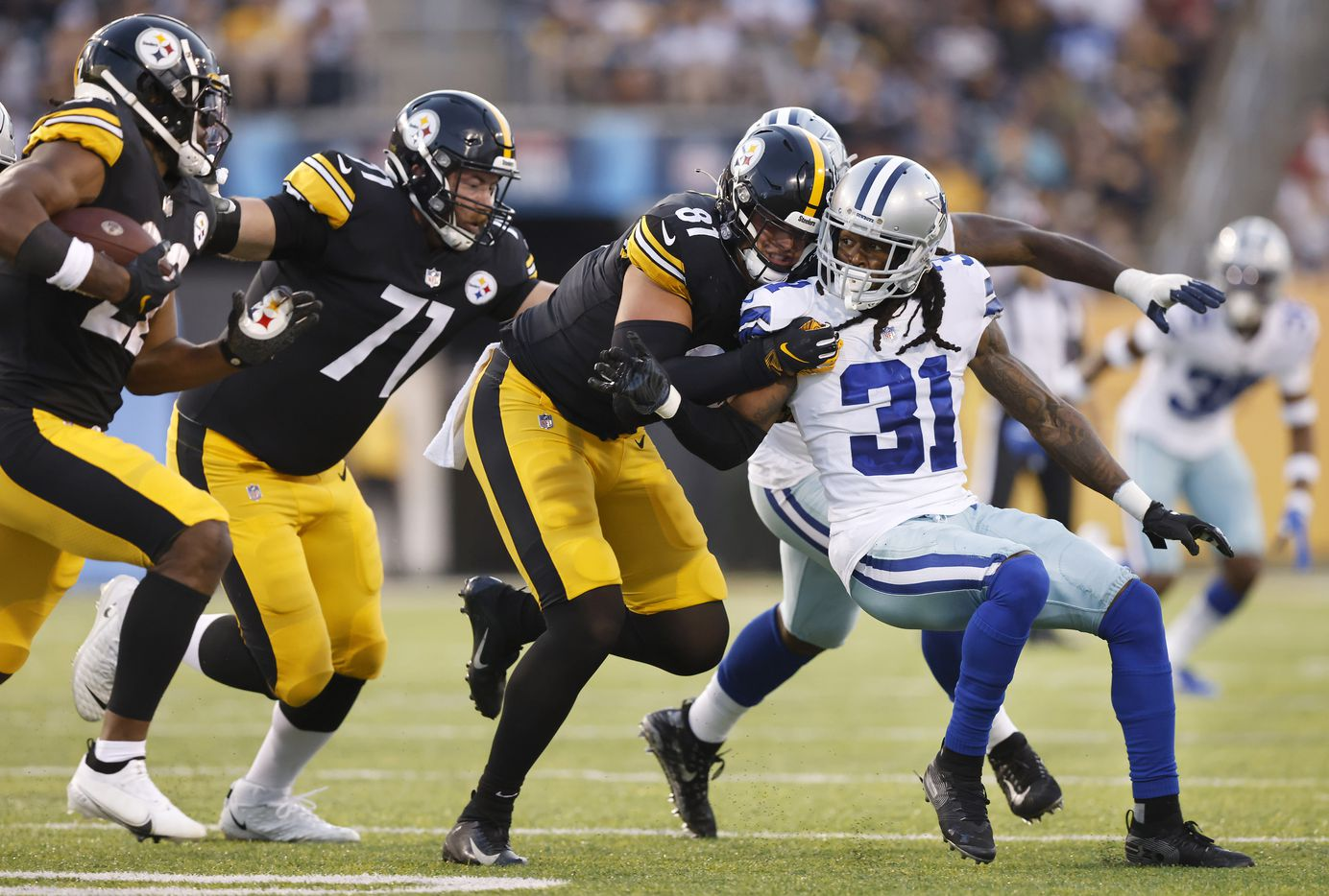 Dallas Cowboys cornerback Maurice Canady (31) fights for traction as he looks to tackle Pittsburgh Steelers running back Najee Harris (22) during the first quarter of their preseason game at Tom Benson Hall of Fame Stadium in Canton, Ohio, Thursday, August 5, 2021. He was being wrestled by Steelers tight end Pat Freiermuth. (Tom Fox/The Dallas Morning News)