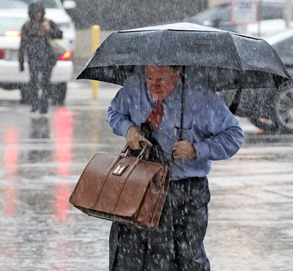 A man made his way through a downpour as he arrived at the Earle Cabell federal courthouse in downtown Dallas on Sept. 26, 2018.