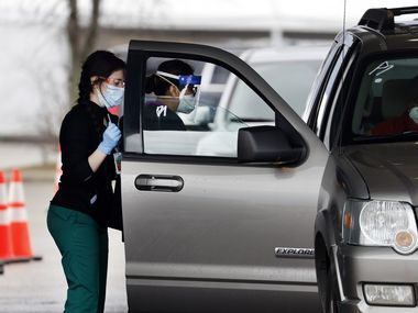 People receive their COVID vaccine in a drive-thru site setup outside the Ellis Davis Field House in Dallas, Monday, March 1, 2021. Beginning April 7, anyone over 16 can be vaccinated at the site without an appointment. (Tom Fox/The Dallas Morning News)