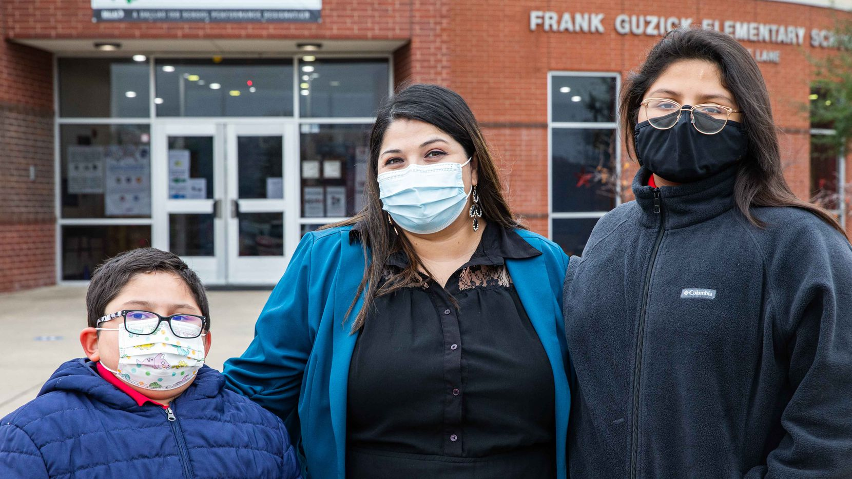 Rosa Mendoza with her two children, David Sanroman, 7, and Miah Rivera-Mendoza, 10, at Frank Guzick Elementary School in Dallas on Tuesday, Dec. 15, 2020. Mendoza has tried to help her kids make progress in math, and says they've thrived since returning to in-person school after months of learning virtually.