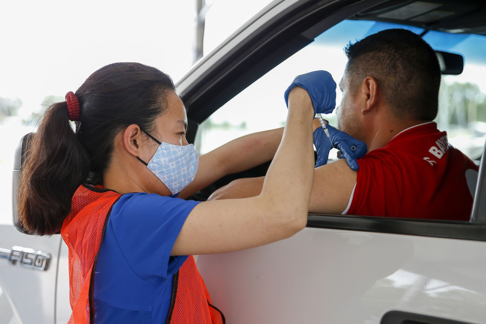 Registered nurse Christine Atayde and an unidentified man help lower the number of unvaccinated by one.