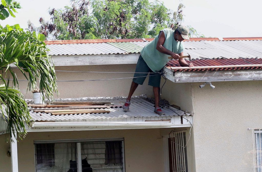 A homeowner makes last-minute repairs to his roof in preparation for Hurricane Irma, in St. John's, Antigua and Barbuda, on Tuesday.