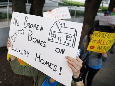 Protesters carried signs outside First Texas Homes' office in Uptown Dallas on Feb. 24, 2020. Felipe Marco was injured on the job and sustained six broken ribs and a perforated lung. Marco has thousands of dollars of medical debt from his injury and was unable to work for weeks. Texas is the only state in the country that doesn't require companies to provide workers' compensation insurance.