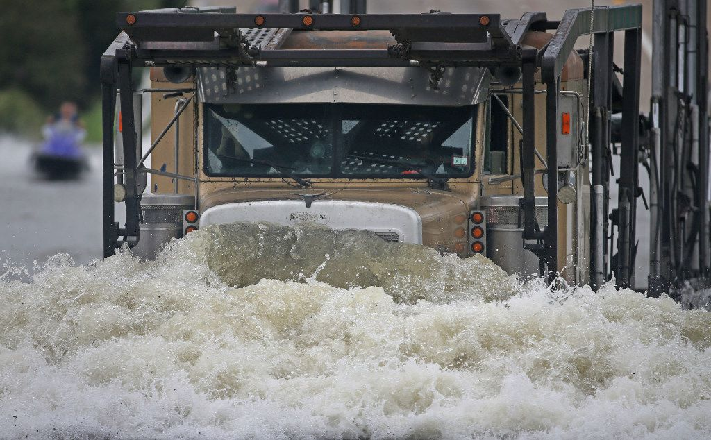 A tractor-trailer rig kicks up foam as it navigates through the flooding on  Intersate 610 south. (Louis DeLuca/The Dallas Morning News)