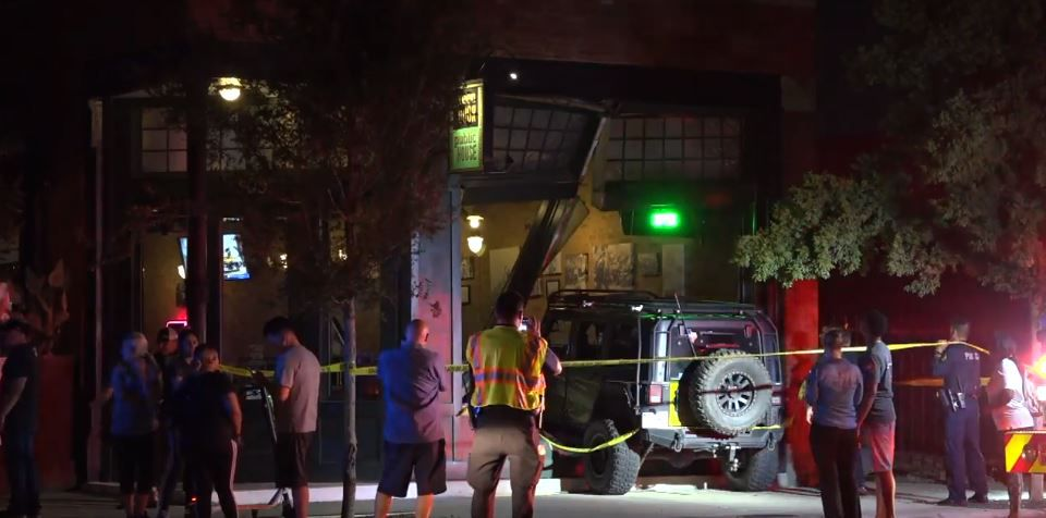 Police and onlookers gather around a Jeep that crashed into the Green Door restaurant around 9:45 p.m. Wednesday.