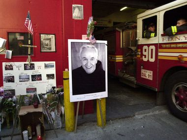 A poster portrait of the late Father Mychal Judge, New York's Fire Department chaplain, is part of a memorial to victims of the World Trade Center attacks outside of Engine Co. One/Ladder Co. 24 in midtown Manhattan in this Sept. 2001 file photo.