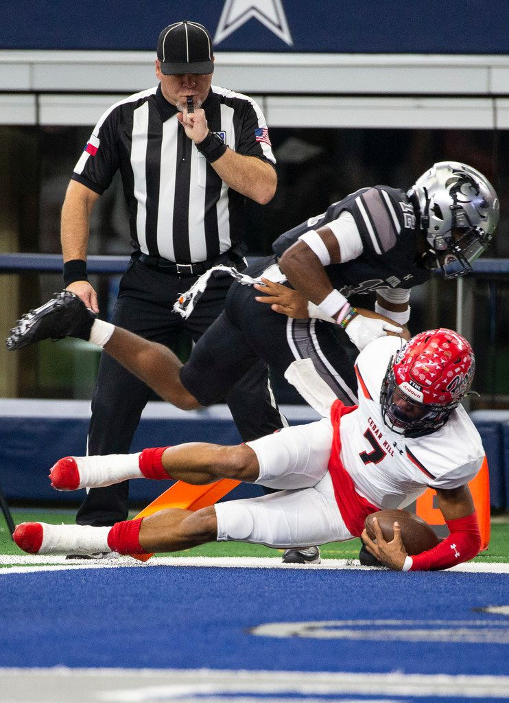Cedar Hill quarterback Kaidon Salter (7) makes the first game touchdown after maneuvering away from Denton Guyer defensive back Deuce Harmon (12) during the first quarter of the Class 6A Division II area-round high school football playoff game at the AT&T Stadium in Arlington, Texas, on Saturday, November 23, 2019. (Lynda M. Gonzalez/The Dallas Morning News)