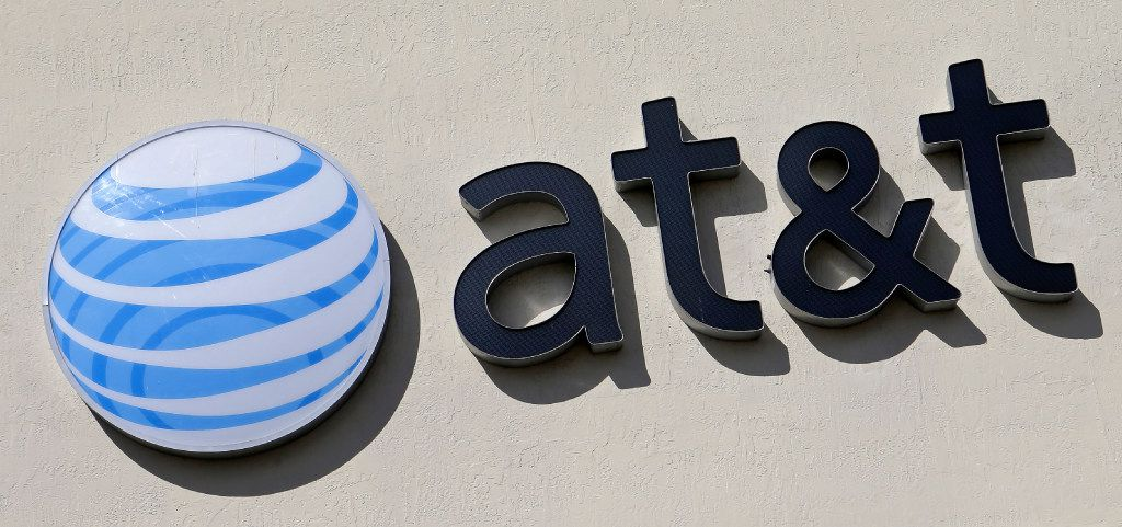 This Feb. 8, 2017, file photo shows the AT&T sign at a store in Hialeah, Fla.