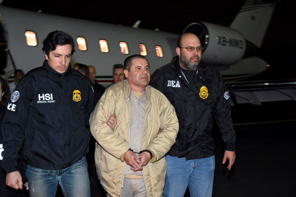 "In this Jan. 19, 2017, photo provided by U.S. law enforcement, authorities escort Joaquin ""El Chapo"" Guzman, center, from a plane to a waiting caravan of SUVs at Long Island MacArthur Airport, in Ronkonkoma, N.Y. The Mexican drug lord is currently on trial in New York City."
