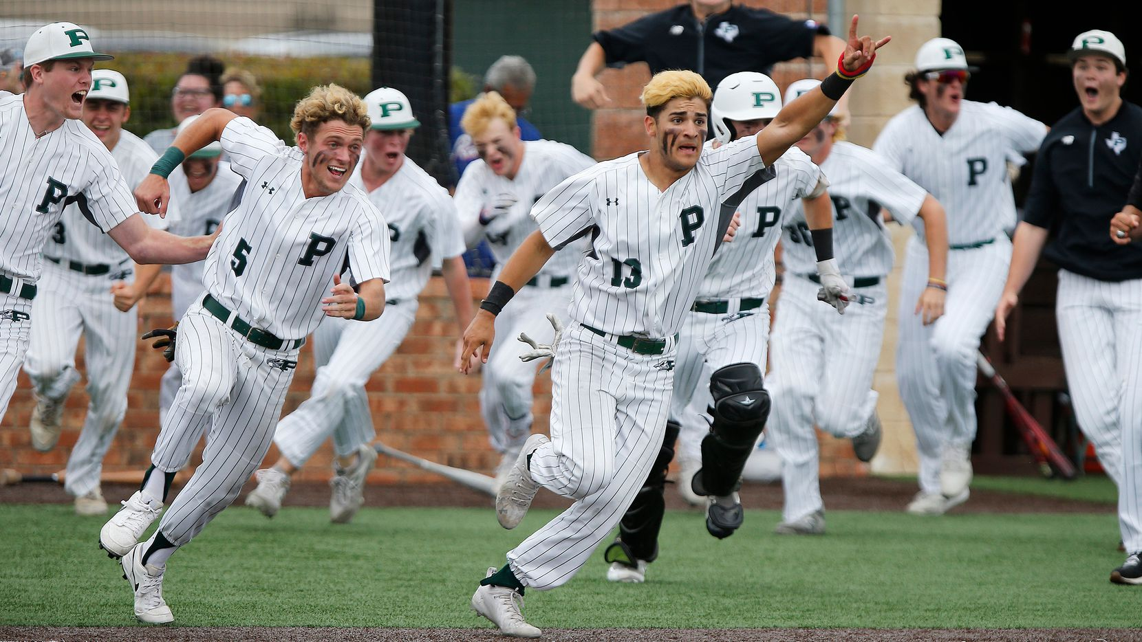 Gabriel Colina (13) leads his team sprinting out of the dugout after completing a come from behind win in their last at bat as Prosper High School hosted Arlington Martin High School in a series final 6A Region I area round playoff game on Saturday afternoon, May 15, 2021. (Stewart F. House/Special Contributor)