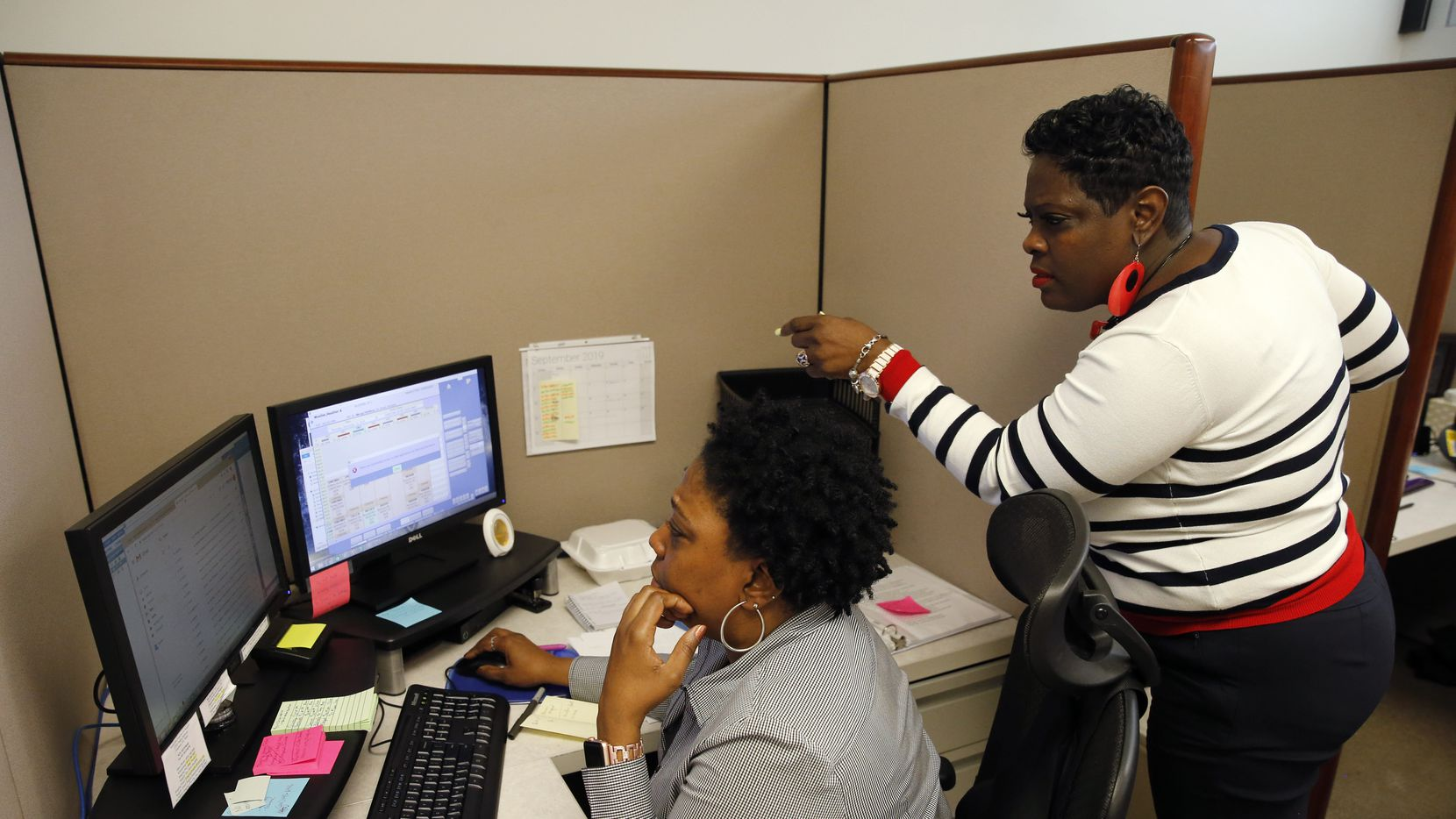 Tangela Matthews (left) and Yolanda Morris work in the central scheduling office at Methodist Hospital for Surgery in Addison.