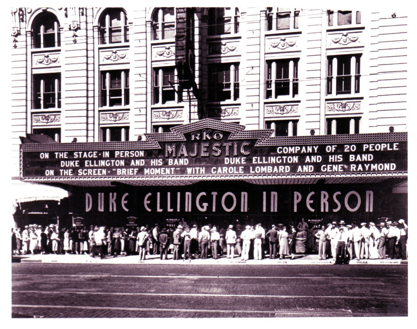 Crowds of people stand outside the theater in 1933, as the marquee advertises a visit from Duke Ellington.