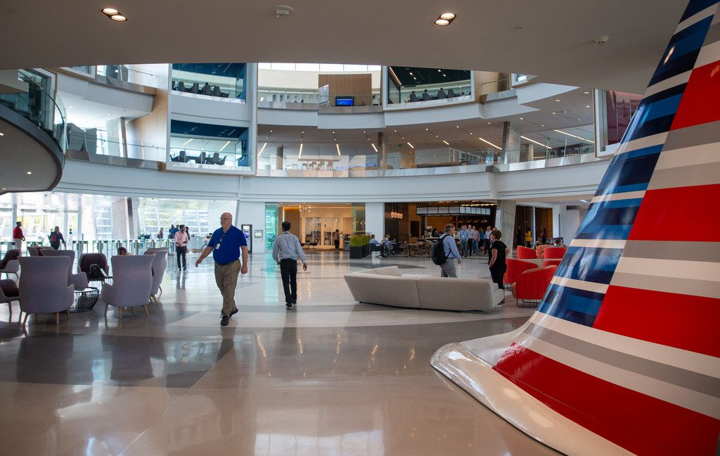 Employees walk through the main lobby of the Skygate 8 building at the new American Airlines campus and headquarters in Fort Worth on Monday.