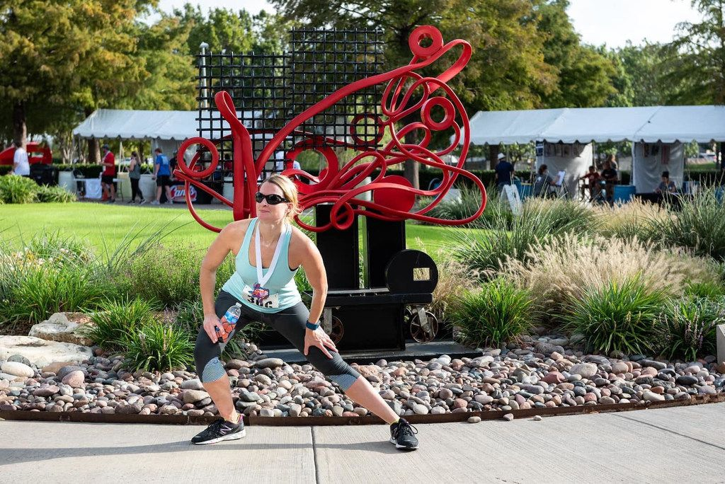 A participant at the Frisco Arts Walk & Run 2018 pauses for a stretch at the Texas Sculpture Garden.
