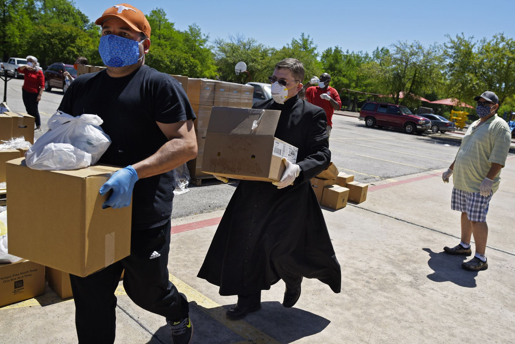 Catholic volunteers from Dallas Area Interfaith and Pastor Gaston Giacinti (center) carry boxes of food to give to families in need during a drive-through  delivery at St. Bernard of Clairvaux Catholic Church in Dallas on April 29, 2020.