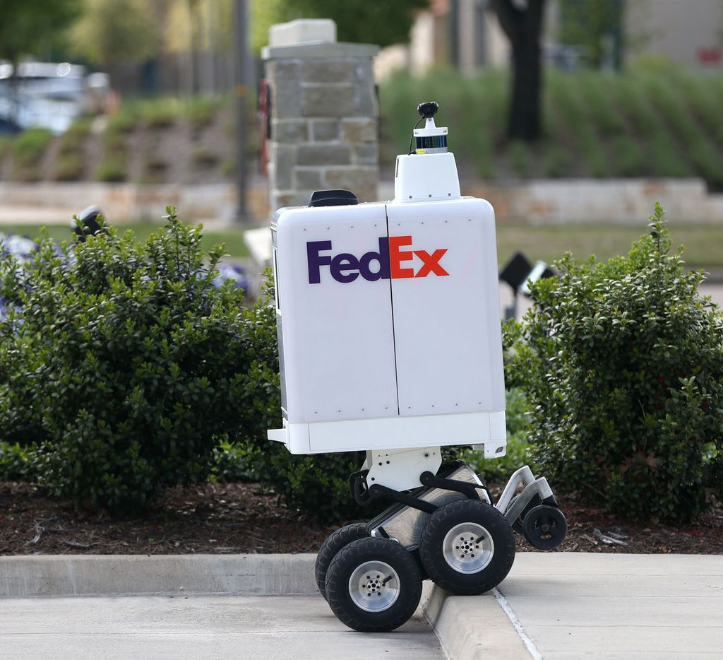 The FedEx same-day bot ascends a curb during a demonstration outside the FedEx Office headquarters in Plano. The bot will be tested in Frisco and Plano with plans to deliver Pizza Hut pizza, Target or Walmart items or prescriptions to customers' doors.