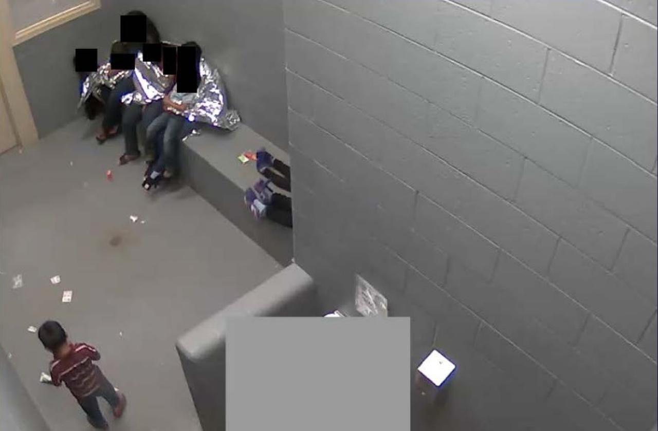 En esta imagen tomada de un video y difundida por el American Immigration Council se observa a niños y adultos detenidos en el centro transitorio de Naco, en Arizona.