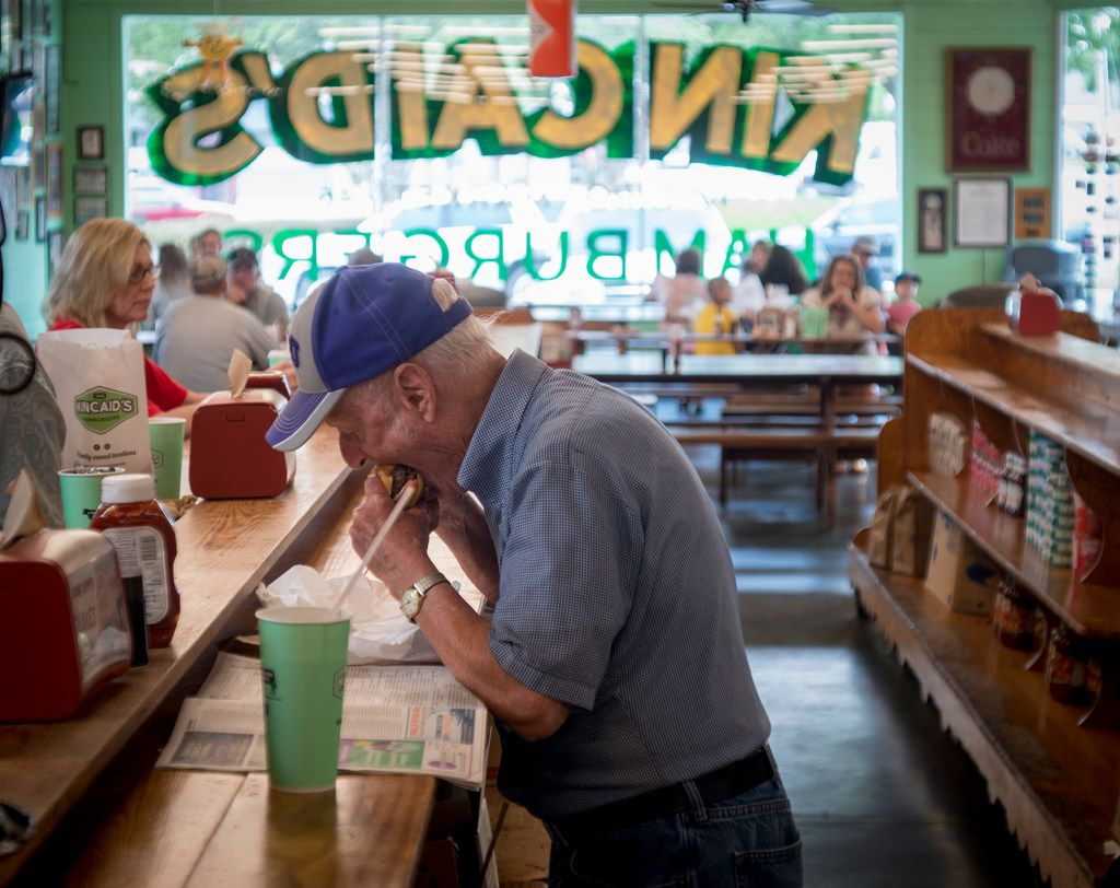 A patron chows down on a burger at Kincaid's on Camp Bowie in Fort Worth.