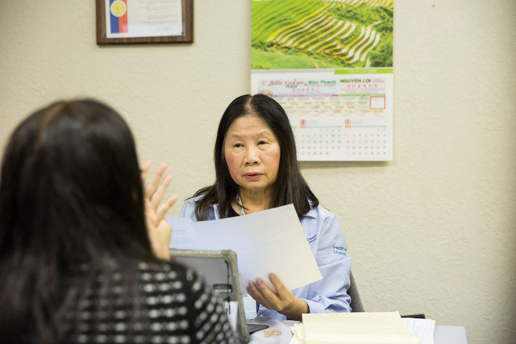 Lisa Pham (right), a Vietnamese-speaking health insurance marketplace navigator, speaks with her client, Mua Thi Nguyen, at the Vietnamese community center in Pantego, Texas, on Nov. 8, 2017.