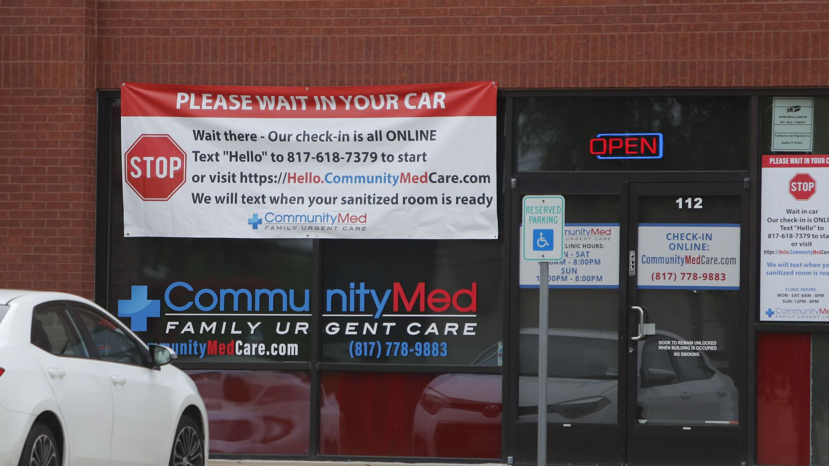 A car sits outside an urgent care facility in Arlington, Texas, Monday, March 23, 2020. In response to the COVID-19 outbreak, CommunityMed Urgent Care implemented a virtual waiting room for their medical clinics where patients can social distance and wait in their cars before heading into an exam room.