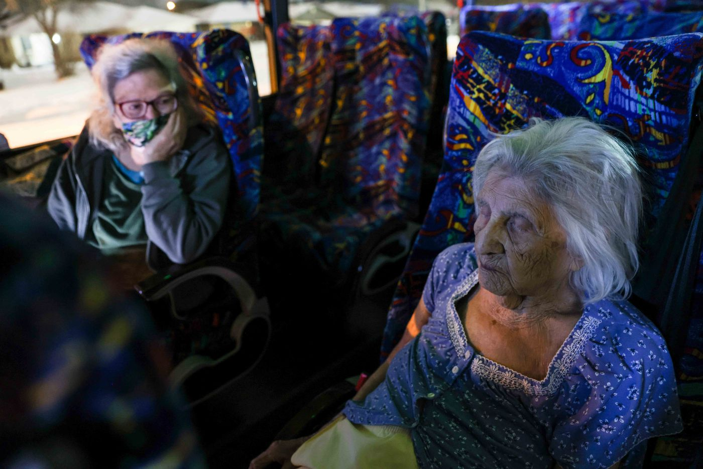 Gloria Sanders, 76, looks at her mother, Maria Barajas, who is 100 years old and has dementia, as she sleeps on a bus that serves as a warming center located at Pleasant Oaks Recreation Center on Wednesday, February 18, 2021 in Dallas. Their home has been without power since early Monday after the snowstorm hit Texas last Sunday.