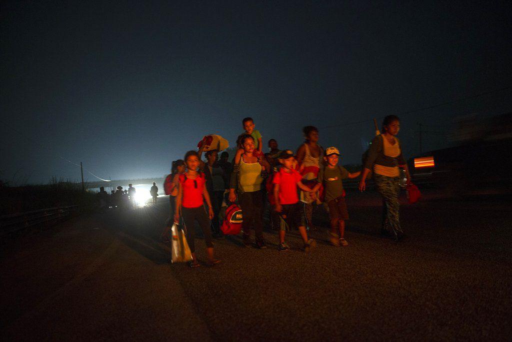 Una familia camina junto a otros migrantes centroamericanos en una caravana de miles de personas que lentamente se dirige a la frontera entre México y Estados Unidos, en las afueras de Arriaga, México, antes del amanecer del sábado 27 de 2018. (AP Foto/Rodrigo Abd)