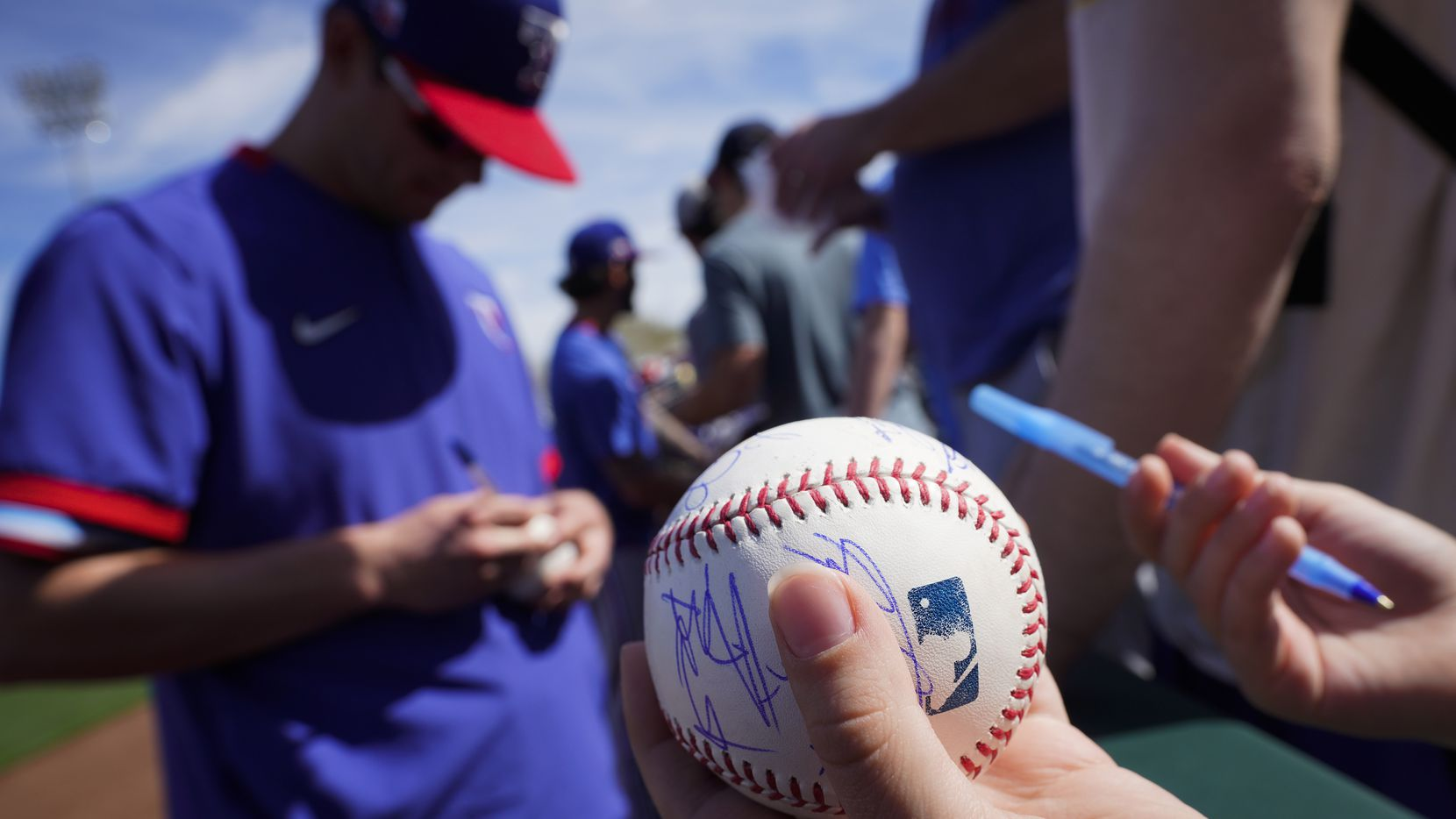 Texas Rangers infielder Nick Solak signs autographs before a spring game against the Kansas City Royals at Surprise Stadium in Surprise, Ariz., a short drive from Phoenix.