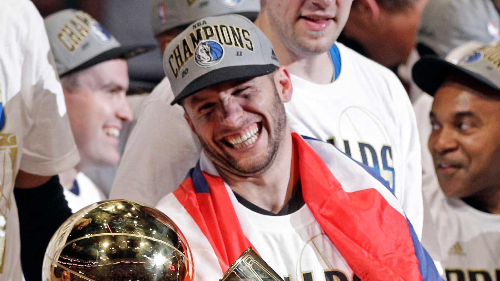 Dallas Mavericks' Jose Juan Barea holds up the championship trophy after Game 6 of the NBA Finals basketball game against the Dallas Mavericks Sunday, June 12, 2011, in Miami. The Mavericks won 105-95 to win the series.