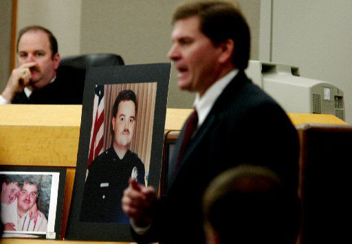 A photograph of Irving police Officer Aubrey Hawkins sits between then-state District Judge Vickers Cunningham and then-Dallas County prosecutor Toby Shook during Shook's closing arguments during Randy Halprin's capital murder trial in 2003 . Halprin, who is Jewish, says in a federal appeal that Cunningham's anti-Semitic remarks and beliefs should have prevented him from presiding over his trial. Halprin is  on death row.
