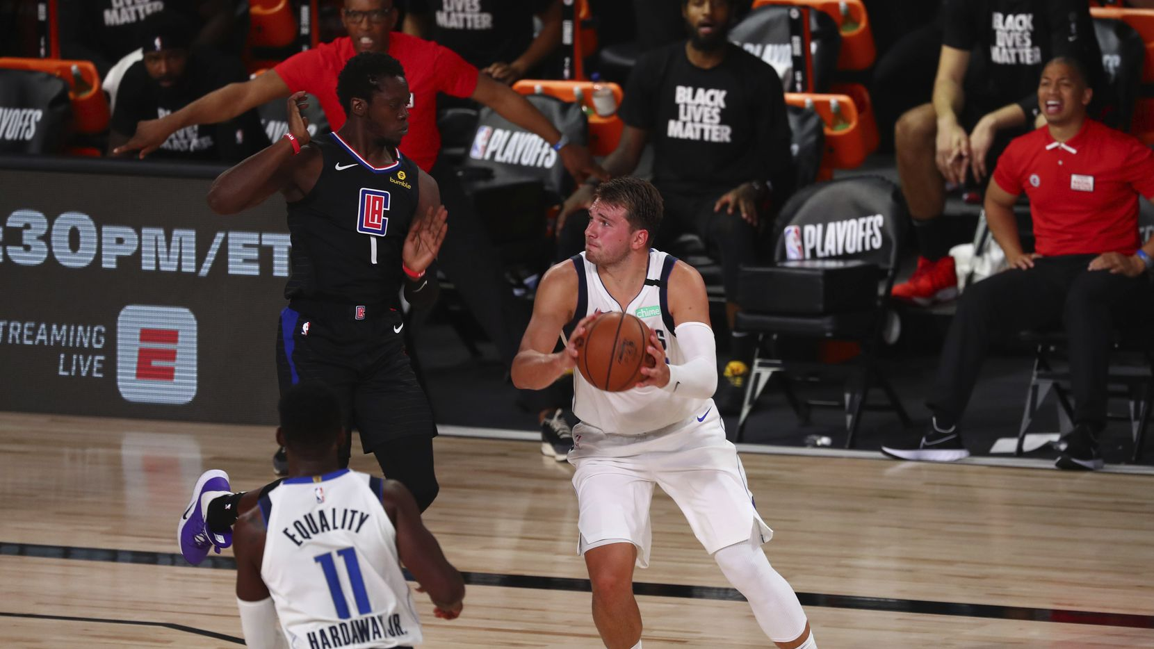 Los Angeles Clippers' guard Reggie Jackson (1) fouls Dallas Mavericks guard Luka Doncic (77) in the second half  of Game 1 of an NBA basketball first-round playoff series, Monday, Aug. 17, 2020, in Lake Buena Vista, Fla. (Kim Klement/Pool Photo via AP)