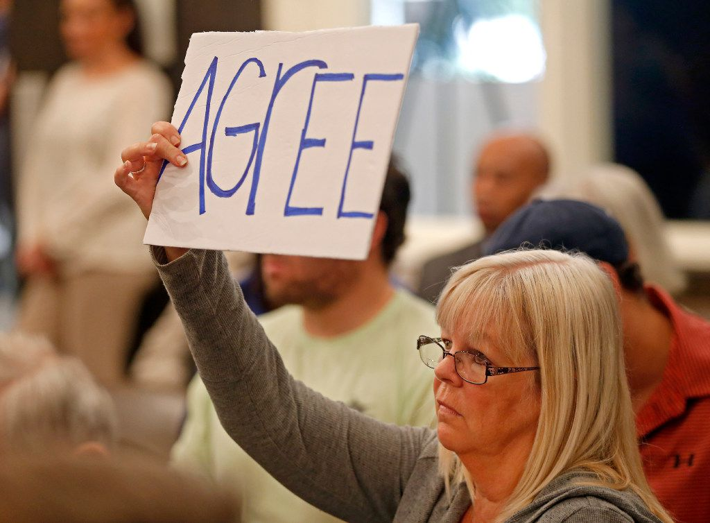 Monica Fanhorn holds up a sign at Rep. Joe Barton's town hall meeting at Corsicana Government Center in Corsicana on Tuesday. Barton answered questions on a variety of topics, including a health care plan, during the Q&A session. (Jae S. Lee/The Dallas Morning News)