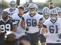 El jugador Isaac Alarcón (#60) corre junto a otros jugadores de los Cowboys de Dallas en el primer día de entrenamientos en la sede del equipo en Frisco, Texas.