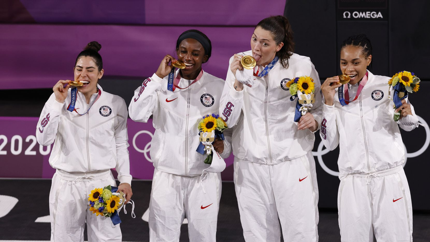 USA's Kelsey Plum (5), Jacquelyn Young (8), Stefanie Dolson (13), and Allisha Gray (15) pose for photos during the medal ceremony for the 3x3 women's basketball final at the postponed 2020 Tokyo Olympics at the Tokyo Aomi Urban Sports Park on Wednesday, July 28, 2021, in Tokyo, Japan.