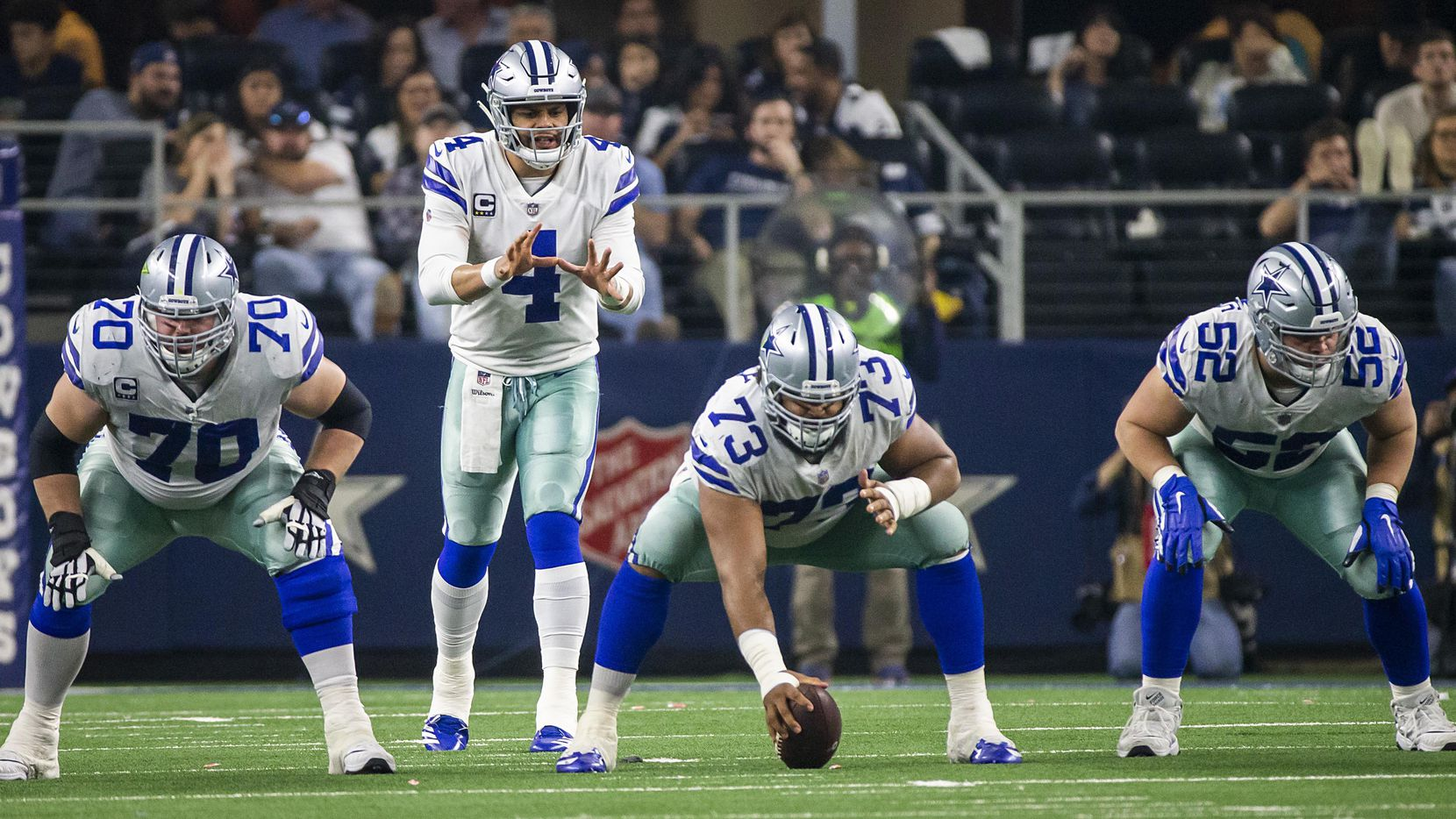 Dallas Cowboys quarterback Dak Prescott (4) lines up behind offensive guard Zack Martin (70), center Joe Looney (73) and offensive guard Connor Williams (52) during the second half of an NFL wild-card playoff football game against the Seattle Seahawks at AT&T Stadium on Saturday, Jan. 5, 2019, in Arlington. The Cowboys won the game 24-22.