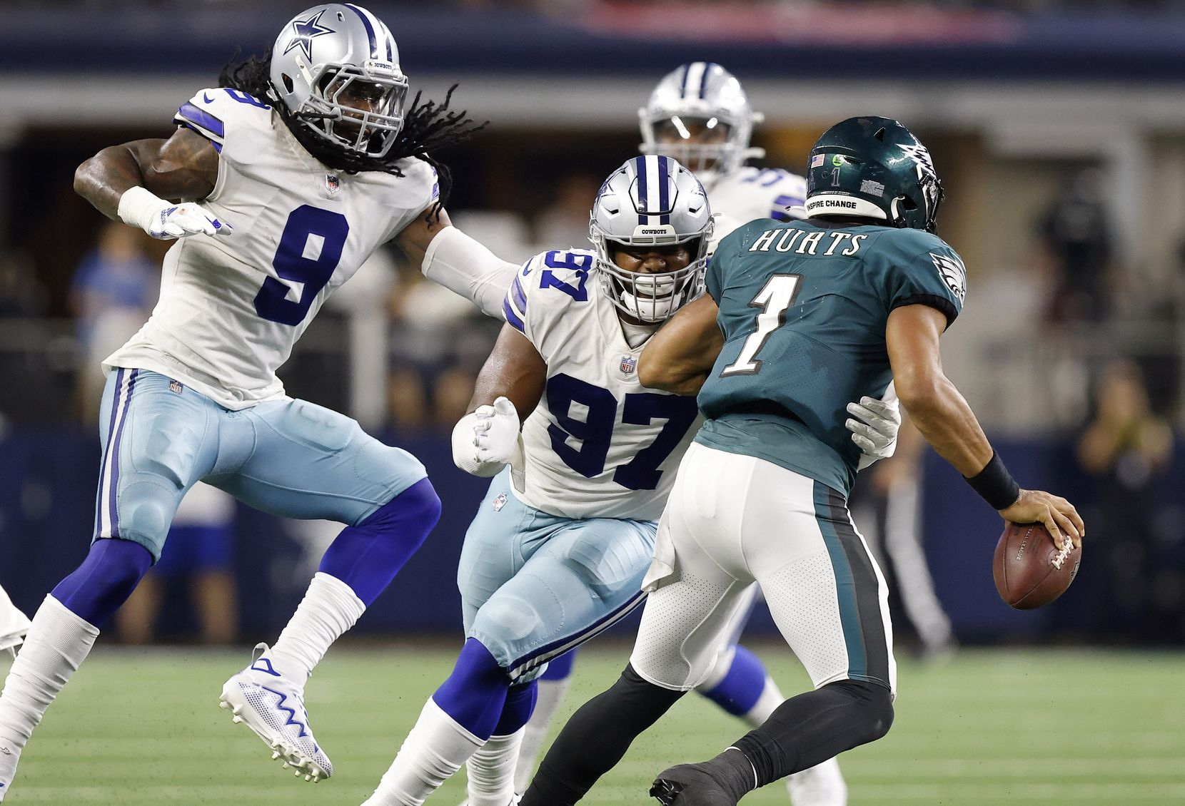 Dallas Cowboys defensive tackle Osa Odighizuwa (97) wraps up Philadelphia Eagles quarterback Jalen Hurts (1) for a fourth quarter sack at AT&T Stadium in Arlington, Monday, September 27, 2021. Middle linebacker Jaylon Smith (9) joined in on the defensive play.