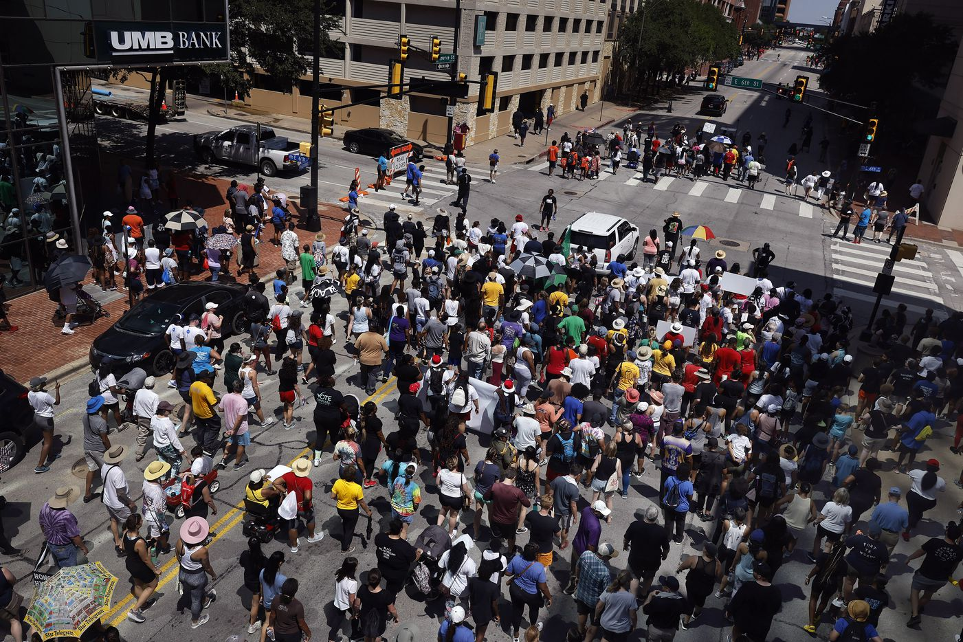 A large group of supporters follow Opal Lee (under umbrellas, top) down Commerce St. during her Juneteenth walk event through downtown Fort Worth, Saturday morning, June 19, 2021.