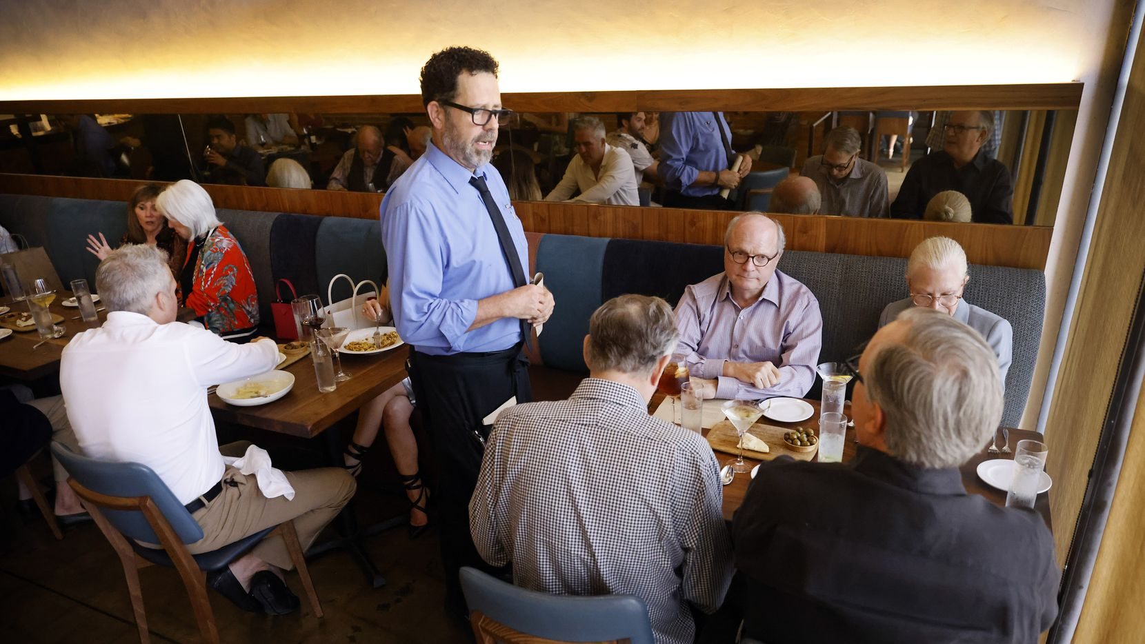 Server David Walsh waited on a table at the nearly full Nonna restaurant in Dallas on Friday evening, July 2.