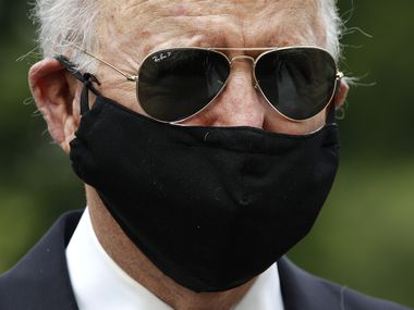 In this May 25, 2020, photo former Vice President Joe Biden wears a face mask to protect against the spread of coronavirus as he and Jill Biden depart after placing a wreath at the Delaware Memorial Bridge Veterans Memorial Park in New Castle, Del.