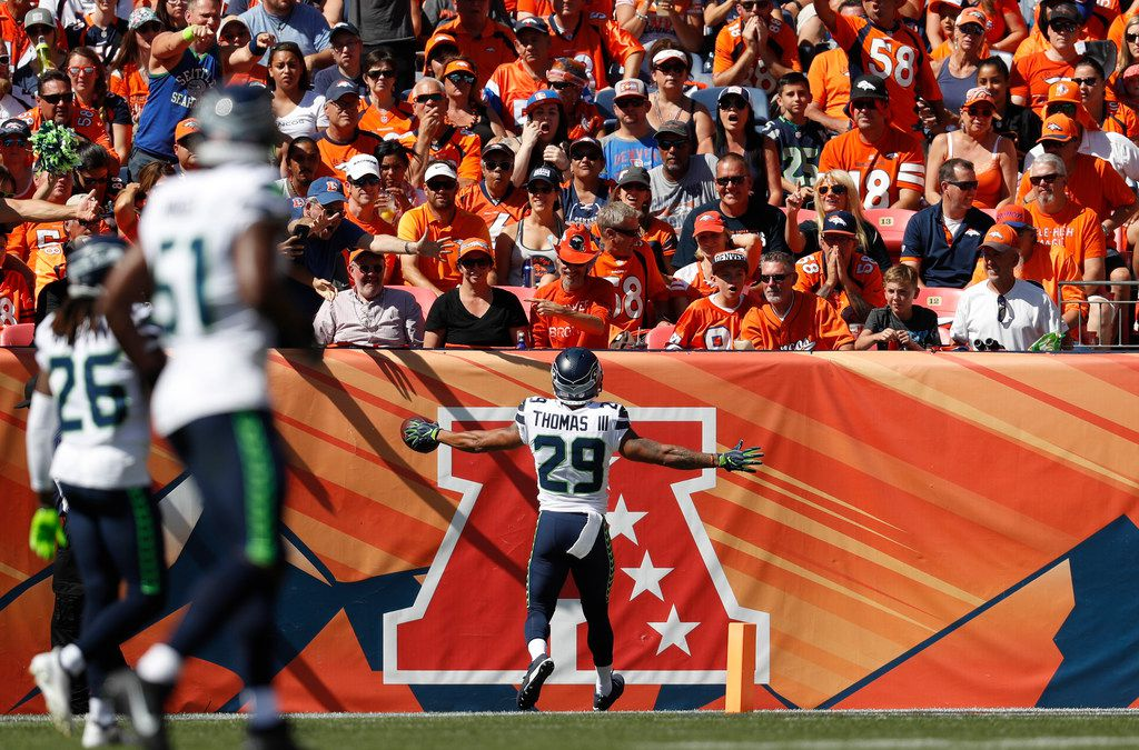 Seattle Seahawks safety Earl Thomas, center, reacts after an interception during the first half of an NFL football game against the Denver Broncos, Sunday, Sept. 9, 2018, in Denver. (AP Photo/David Zalubowski)