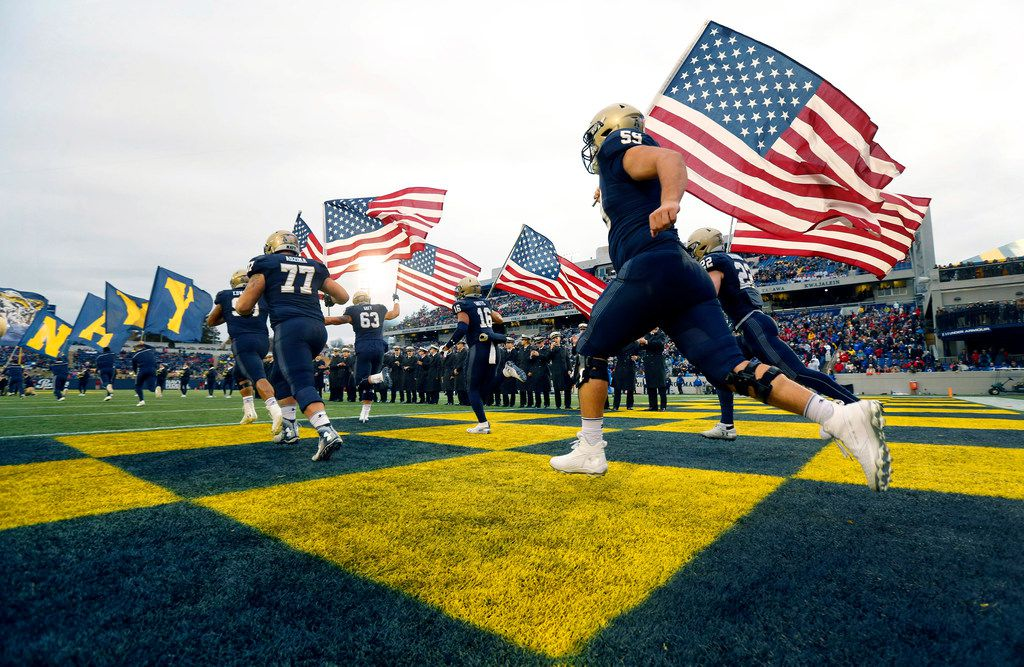 The Navy Midshipmen take the field with U.S. Flags on Senior Day at Navy-Marine Corps Memorial Stadium in Annapolis, Maryland, Saturday, November 23, 2019. The Midshipmen were facing the Southern Methodist Mustangs. (Tom Fox/The Dallas Morning News)