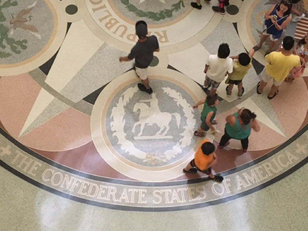 Tourists stride across the floor of the Capitol rotunda in Austin on Thursday, June 9, 2016. The floor depicts seals from the six powers that have at some point held control over Texas land, including the Confederate States of America.