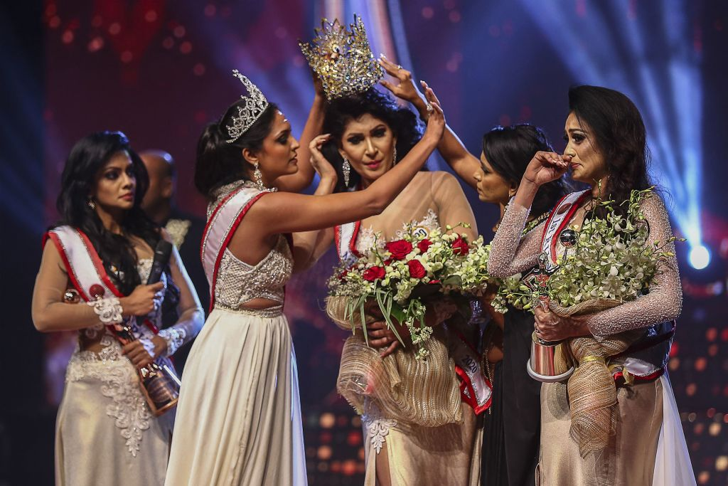 En esta foto tomada el 4 de abril de 2021, Mrs. Sri Lanka 2020, Caroline Jurie (segunda desde la izq.) le quita la corona a la ganadora del concurso de belleza 2021, Pushpika de Silva (centro) tras acusarla de ser divorciada, lo cual iba en contra de las reglas. Más tarde se confirmó que los señalamientos eran incorrectos.