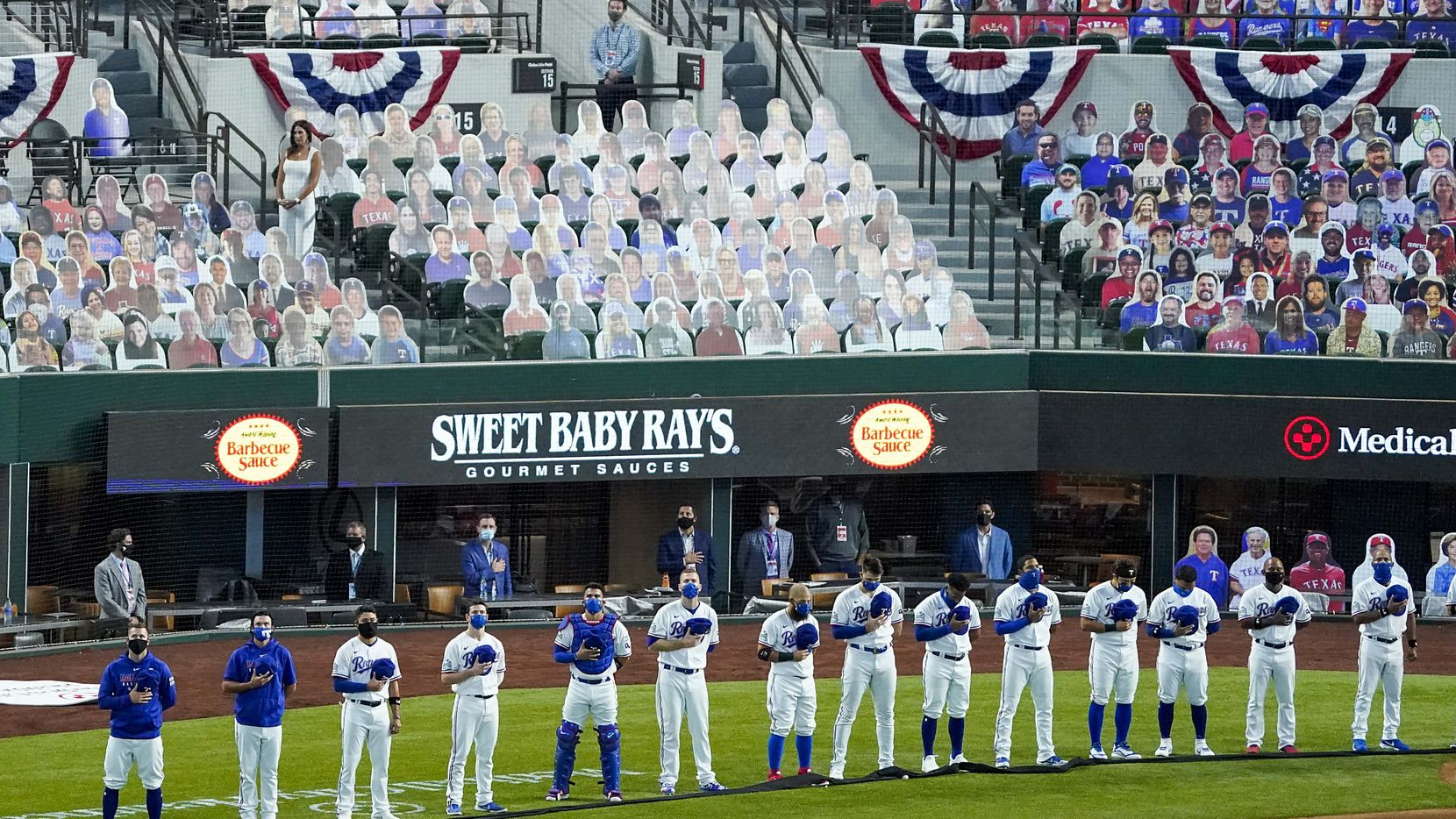 In front of a sea of cutout photos, , Texas Rangers players stand during the singing of the national before playing the Colorado Rockies on opening day at Globe Life Field on Friday, July 24.