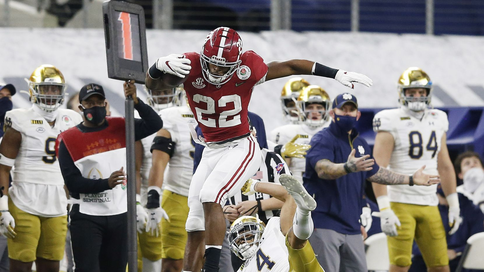 Alabama Crimson Tide running back Najee Harris (22) leaps over Notre Dame Fighting Irish cornerback Nick McCloud (4) on a play during the first half of play at the Rose Bowl NCAA college football playoff semifinal at AT&T Stadium on Friday, December 30, 2020 in Arlington, Texas.
