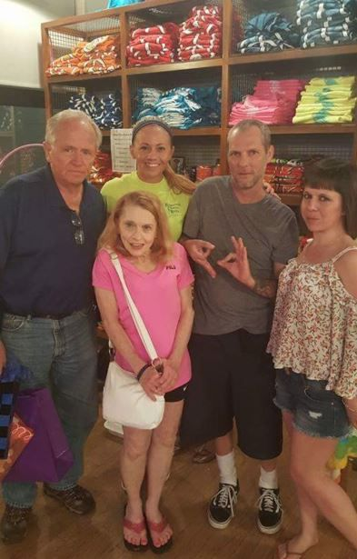 """Dallas police Officer Amber Guyger with her family at Joe's Crab Shack in 2016. Guyger's brother-in-law, Noe Garza, has been accused of making white supremacist hand signals in this photo. He said he is making a """"6"""" and a """"9"""" because they were celebrating Guyger's father's birthday."""